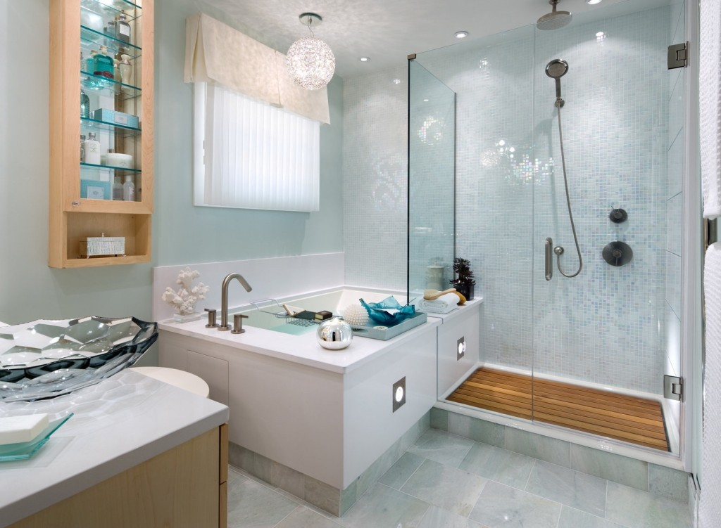 Updated bathroom design with light blue walls and decor, glass shower, round chandelier ball above the tub area, glass sink bowl and tiled floor.