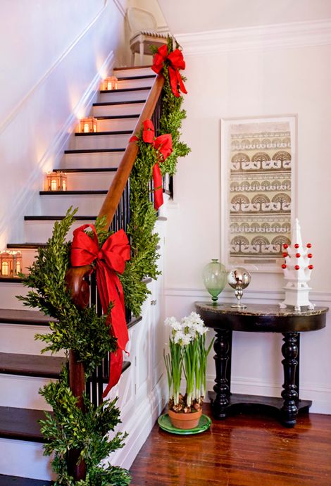 boxwood garland with red bows and lanterns on the stairs